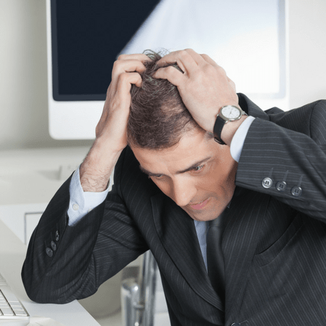 man pulling his hair considering surgical vs non surgical hair replacement treatments