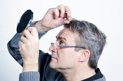Guy checking out his hair with a mirror