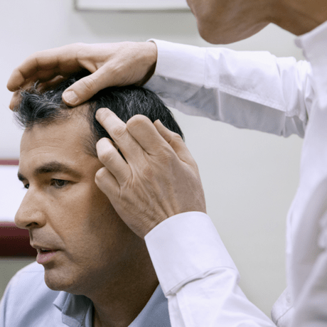 Man being examined at hair loss clinic- new news for the best hair loss treatment