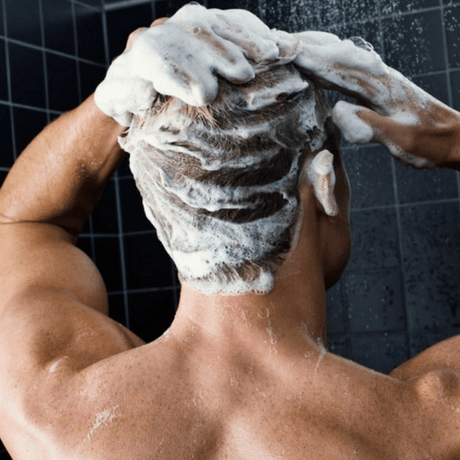 man washing hair with shampoo- claims against suave shampoo hair loss