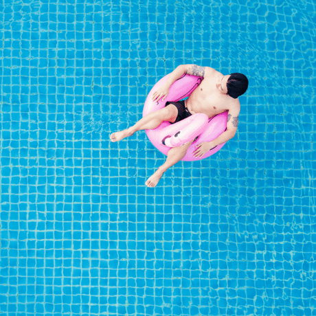 avoiding hair loss anxiety this summer- man chilling in a swimming pool care free