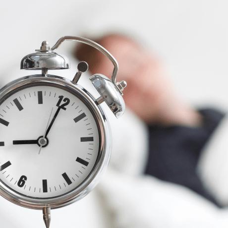 man sleeping with alarm clock