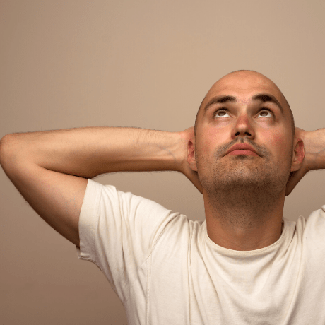 man with shaved head looking up